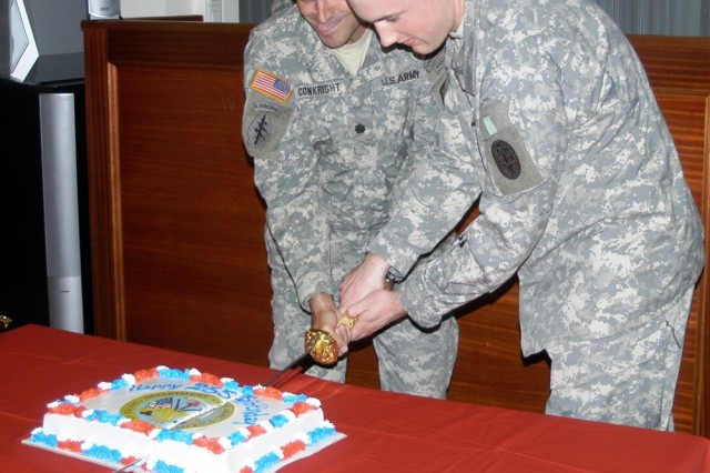 Lt. Col. Darin Conkright, commander of U.S. Army Garrison Brussels, Belgium, and the youngest Soldier in Brussels, Pfc. Chris Newman, slice the Army Birthday cake in front of the assembled garrison's celebration of the Army Birthday.