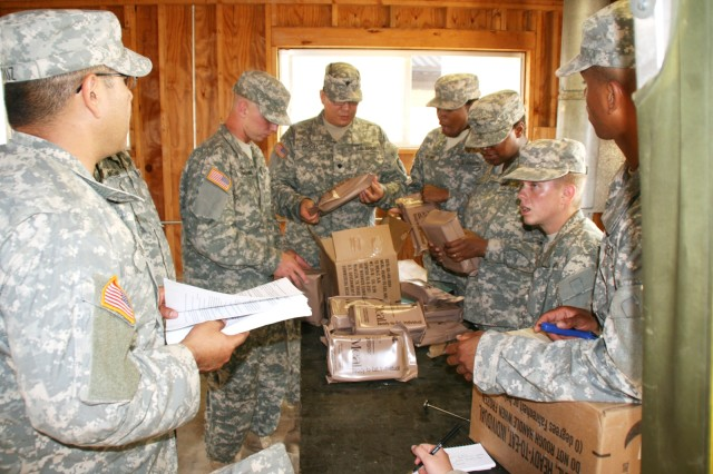 Veterinary food inspection specialists at the Army Medical Department Center and School, Department of Veterinary Science, Food Safety and Defense Branch, perform surveillance inspections of menu bags of Meals Ready to Eat during their field training at Camp Bullis.
