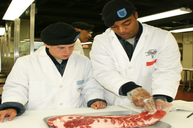 Pvt. Nicholas Brown (left) and Spc. DeWayne Grant classify a cut of meat by reviewing the muscle, ensuring they have the proper cut of meat. The Soldiers are training to become veterinary food inspection specialists during an eight-week course at the Army Medical Department Center and School.