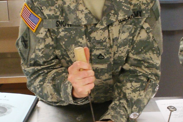 Spc. Rachel Snow performs a temperature check of eggs during hands-on training. Veterinary food inspection specialists perform egg product surveillance and sampling.