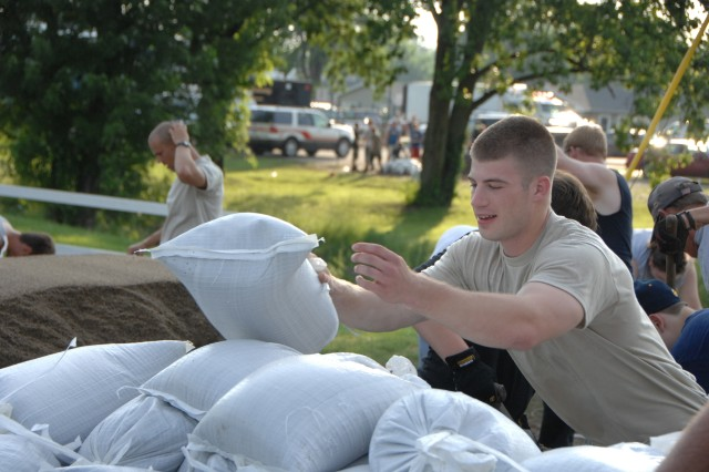 Spc. Joseph Stamm, 1st Battalion, 151st Infantry, helps citizens load sandbags into their vehicle in Martinsville, Ind., June 7. Flash floods tore through the area after over 10 inches of rain poured over the already saturated land.