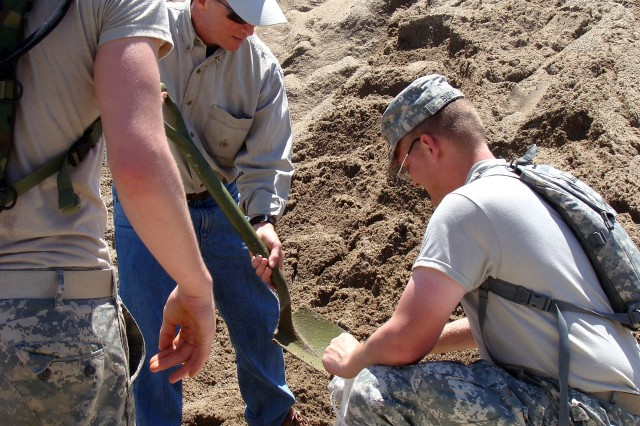 Governor Mitch Daniels of Indiana shovels sand into bag held by Spc. Vance Smith, tied by Spc. John Burke. The Soldiers of the 138th Quartermaster Company in Brazil, Ind., were visited by the Indiana governor during flood efforts along the White River in southwestern Indiana.
