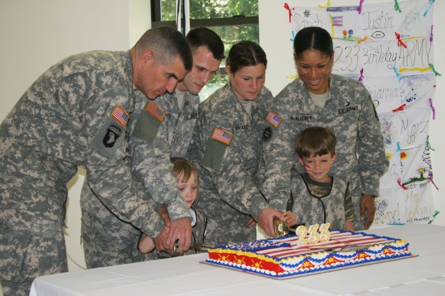 """Brigadier Gen Michal S. Linnington (left), U.S. Military Academy Commandant of Cadets; Morgan Humphrey; daughter of Maj. and Mrs. Ian Humphrey; 2nd Lt.  Brandon C. Whitten, the youngest officer at West Point; Morgan Humphrey; daughter of Maj. and Mrs. Ian Humphrey; West Point Garrison Command Sgt. Maj. Violet McNeirney; Jason Cochran, son of Sgt. 1st Class and Mrs. Brian Cochran; Pfc. Ramona Barnard, the youngest West Point Soldier make the ceremonial first cuts using both officer and an NCO sabers while the rest of the attendees sang """"Happy Birthday"""" during the cake cutting at West Point's celebration of the 233rd Army birthday June 13.    Photo by Spc. Vincent Fusco/West Point Directorate of Communications"""