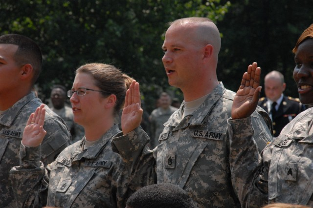Sgt. 1st Class Margaret Hood and her husband Staff Sgt. Mark Hood re-enlist in a Pentagon ceremony on June 13.