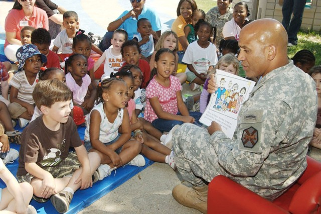 """Col. Anthony D. Reyes, Garrison Commander at Fort Monroe, Va., reads a new book titled """"Happy Birthday Army"""" - produced by the Army Family Morale Welfare and Recreation Command - to youngsters at the installation\'s Child Development Center on June 13. The youth celebration also included the singing of """"Happy Birthday"""" and cake. Each of the children received a copy of the book. (Photo by Patricia Radcliffe)"""