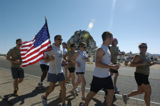 Runners pass the Painted Rocks at Fort Irwin, Ca. during the first mile of the Run for the Fallen. President of the run, Jon Bellona carries the American flag that will be handed off to the next runner as they relay across the United States. The run will take approximately 72 days and will cross thirteen states from Painted Rocks at Fort Irwin Ca, to Arlington National Cemetery, Va.  The purpose of the run is to honor all of the Service members lost in Operation Iraqi Freedom and Operation Enduring Freedom by running one mile in memory of each one.