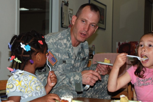 LIVORNO, Italy - LeAire George, left, asks Lt. Col. Steven Cade, commander of U.S. Army Garrison Livorno, Italy, if she can have another slice of cake, while Yuki Claudio, right, enjoys a large bite. The children at the Camp Darby Child Development Center celebrated the 233rd Army Birthday with a special book reading and cake cutting just for them.