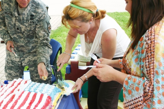 """ANSBACH, Germany - Honoring the Army's 233rd Birthday, Lt. Col. Tammy McKenna, commander of U.S. Garrison Ansbach, Germany; Heather Lammers, Katterbach Child Development Center director; and Judith Vazquez, CDC administration assistant, cut and serve Army birthday cake at the Katterbach CDC June 12. Prior to the cake cutting, McKenna read """"Happy Birthday Army,"""" a book by Army Youth Services to CDC children. The garrison's Child and Youth services hosted numerous events to better include the garrison's younger members in the birthday celebrations."""