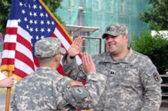 Capt. Michael Weisman, commander of the Bavaria Warrior Transition Unit (right), re-enlists Spc. Angel Gomez in Schweinfurt, Germany June 5. Gomez, injured in combat in Iraq in April 2007, recovered from his injuries in the Bavaria WTU and returned to duty. He is awaiting orders for a new assignment at Fort Benning, Ga.