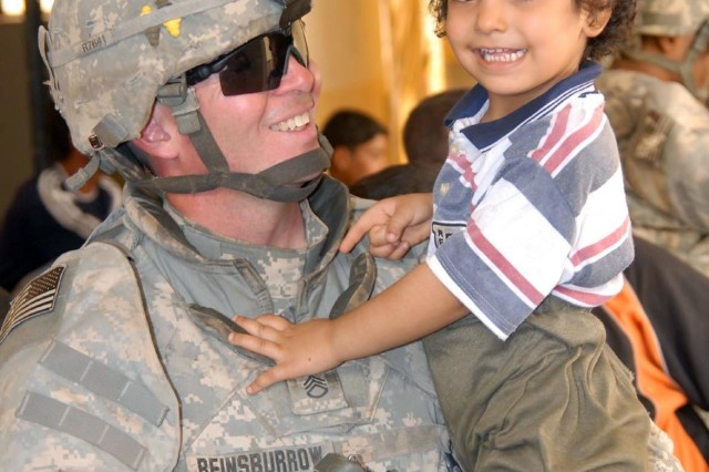 Staff Sgt. Joseph Reinsburrow of the 64th Military Police Company holds an Iraqi child during a joint MP and Iraqi Police mission to hand out toys and school supplies at a girls' school in Hurriyah, Iraq, June 12. The 64th, based at Fort Hood, Texas, is currently operating in Iraq as part of U.S. Army Europe's 18th MP Brigade