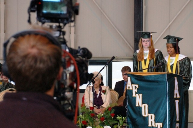 Katherine Brunskill, left, and Makayla Deshazor, salutatorians for the AFNORTH International High School Class of 2008, welcome dignitaries to the ceremony under the lens of a television crew who broadcast a podcast of the entire ceremony to deployed family members via the Internet.