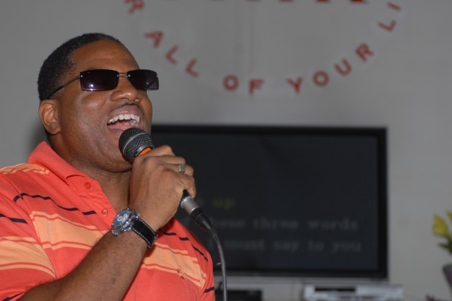 """Walt """"Baby Love"""" Horton, civilian contractor, sings """"I just called to say I love you"""" by Stevie Wonder at the first round of a karaoke competition at MWR 124 June 8."""