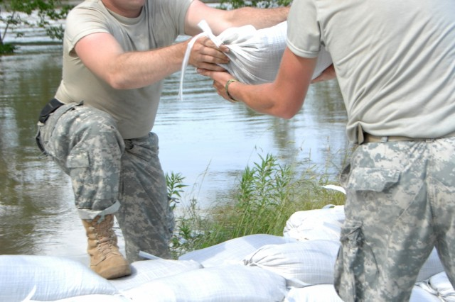 Pfc. Kenneth Edds grabs a sandbag from Spc. Jeremy Tolson in Hazleton, Ind., on June 12, 2008. Sandbagging was a part of Indiana National Guard flood-relief efforts to prevent and protect the town from the rising White River.