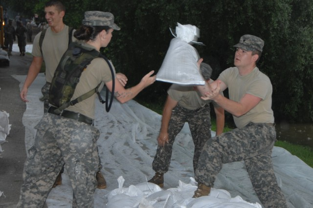 Spc. Bethany Scott throws a sandbag to Spc. Robert Alexander, both of the Indiana National GuardAca,!a,,cs 38th Military Police Company, to help stop water expected to rise to 22 feet at a levee in New Harmony, Ind., June 13, 2008.