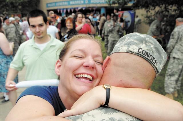 Chris Conger, left, welcomes her husband Sgt. Raymond Conger.
