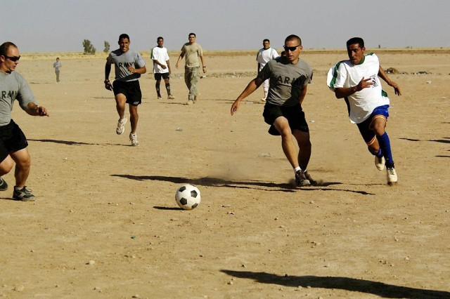 Soccer Warriors of 1st Battalion, 87th Infantry Regiment, scramble for a loose ball Thursday on a dusty field near Mahus in the Hawijah District of the Kirkuk Province, Iraq.
