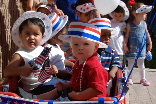 Toddlers ride in a decorated wagon during the Main Child Development Center's Red, White and Blue parade down Haan Road, Fort Bliss, in honor of the Army's 233rd Birthday.
