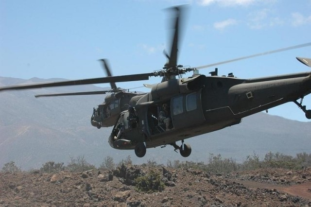 """Two UH-60L Blackhawk helicopters, flown by pilots from the 25th Combat Aviation Brigade's Task Force """"Diamond Head,"""" head towards a landing zone for a planned air assault mission at the Pohakuloa Training Area, on the Big Island of Hawaii,"""