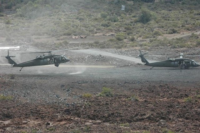 """Two UH-60L Blackhawk helicopters insert Soldiers from Alpha Troop, 3rd Battalion, 4th Cavalry Regiment, 3rd Infantry Brigade Combat Team, 25th Infantry Division during an air assault. The helicopters, from Task Force """"Diamond Head,"""" are part of the 25th Combat Aviation Brigade's joint training with 3rd IBCT, 25th ID at the Pohakuloa Training Area, on the Big Island of Hawaii."""