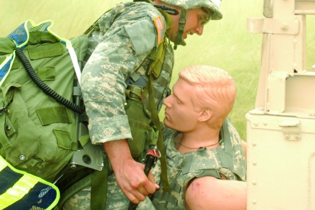 Spc. Daniel Farrier, MEDCOM Soldier of the Year, rescues a mannequin from a damaged vehicle during the combat scenario portion of the competition.