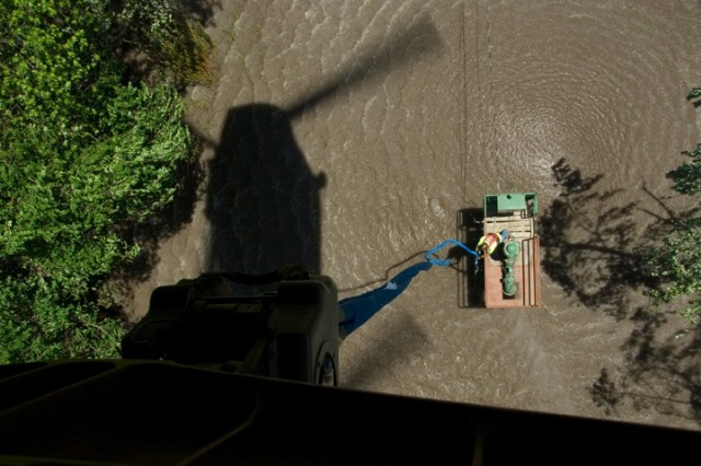 An employee of the Cedar Rapids Water Utility prepares to attach a lift cable from an Iowa Army National Guard CH-47 Chinook helicopter to a damaged water pump on the Iowa River near Cedar Rapids, Iowa. The CH-47 was used recover several water pumps in need of repair following massive flooding caused by heavy rains in Iowa. The pumps will be repaired and put back in place to provide fresh water for the residents of Cedar Rapids. Soldiers throughout the Midwest are assisting with evacuations, search and rescue, security, sandbagging, generator support, providing emergency drinking water, removing debris and repairing damaged infrastructure.
