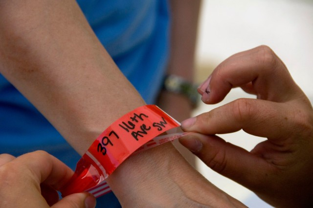 A resident of Cedar Rapids, Iowa, receives a wristband, signifying approval to return home, June 15, 2008. Residents are allowed to return to their homes during designated times to recover personal items and valuables. Soldiers throughout the Midwest are assisting with evacuations, search and rescue, security, sandbagging, generator support, providing emergency drinking water, removing debris and repairing damaged infrastructure.