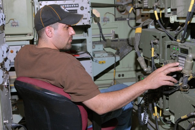 Richard Robinson, an electronics worker at Tobyhanna Army Depot, tests an AN/GRC-245 High-Capacity Line-of-Sight radio during the pre-test part of the AN/TRC-190 radio system Reset process.