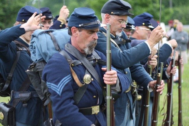 Re-enactors load firearms during a demonstration of Civil War-era military tactics during a living history timeline at Fort Drum June 14 which presented the dress and weapons of warriors from Fort Drum's history.