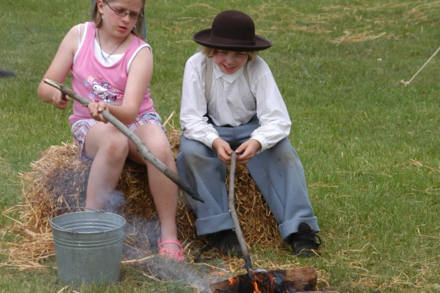 Two children, one in period costume, enjoy a Civil War-era camp site on Fort Drum June 14 during living history timeline.