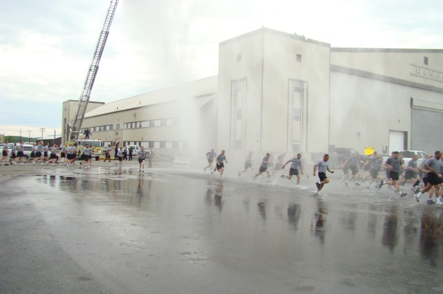 Soldiers of the 1st Stryker Brigade Combat Team, 25th Infantry Division run through spray from the Fort Wainwright Fire Department's truck. More than 3,500 Soldiers participated in the brigade run June 18 to commemorate the Army's birthday.