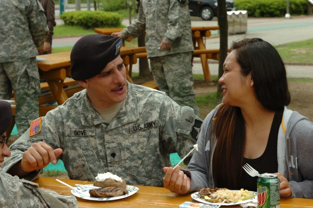 Spc. Eli Dove, HHB, 210th Fires Brigade, talks to a spouse during lunch in New Town Park, Dongducheon June 4.