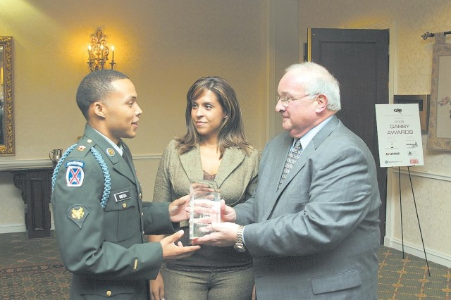 Spc. Channing Moss, Warrior Transition Battalion, accompanied by his wife Lorena, accepts the Georgia Association of Broadcasters Georgian of the Year Award from John Ray, WRDW-TV Channel 12 president and general manager, during the GAB Annual Awards Banquet in Marietta, Ga., June 6, 2008.