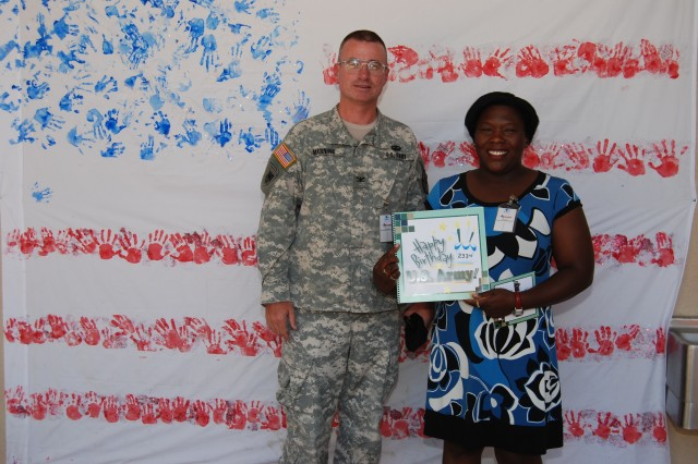Fort Bliss Garrison Commander Col. Edward Manning and Shoshana Johnson, the first American black female prisoner of war with the Fort Bliss 507th Maintenance Company, stand in front of a flag created with 233 children's handprints.
