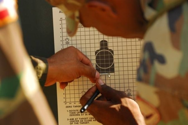 Participants connect the dots on their target range card after the first three shots to check for accuracy during the Fuerzas Comando exercise at Camp Bullis.