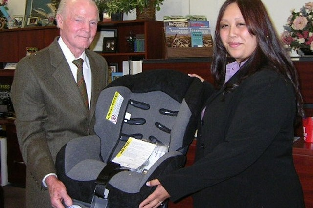 Dempsey Ballard, Government Employees Insurance Company representative, presents  Jai Bell, relocation assistant, with 10 Cosco infant car seats for use by Fort Sam Houston Families to ensure a safer automobile ride for new babies.