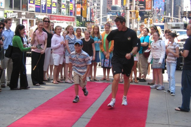 Olympic race-walker Sgt. John Nunn competes here against a young boy in the Times Square Fitness Challenge.