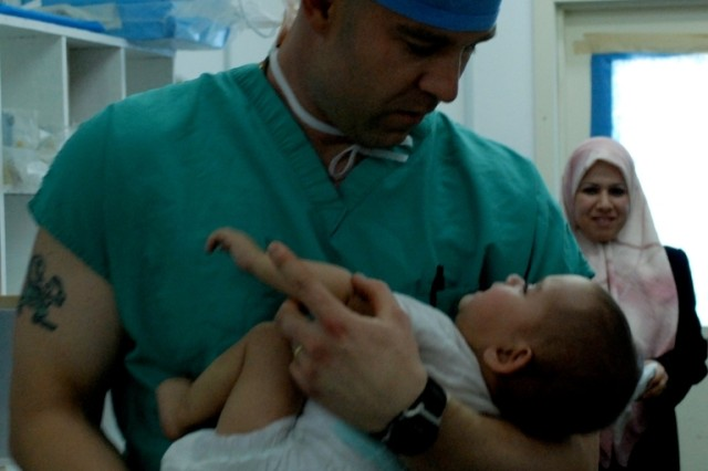 Captain Mike Mullaly, an operating room nurse anesthesist attached to the 948th FST, carries Noor into the operating room with her mom, Zainab Najy standing by. The infant received several life-saving procedures at the FOB Delta medical facility this spring. She will undergo reconstructive surgery in Boston June 30.