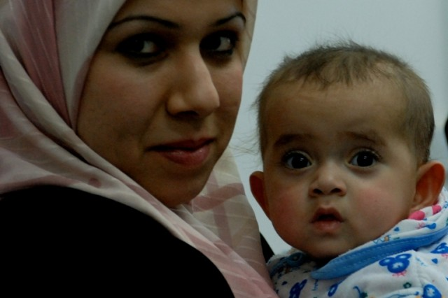 Zainab Najy holds her daughter, Noor, at the FOB Delta medical facility before the infant received several life-saving procedures this spring. She will undergo reconstructive surgery in Boston June 30.