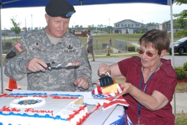 Chaplain (Lt. Col.) R. Gary Moore cuts the Army birthday cake during the Bryan Village youth center bash, June 12. (United States Army Photo by Lina Satele).