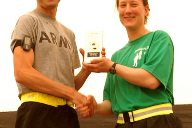 Christopher Lawrence, 10th Mountain Division (Light) band, first place male winner at 31 minutes, receives his trophy at Victory Stage South, Camp Victory, Iraq, June 8.