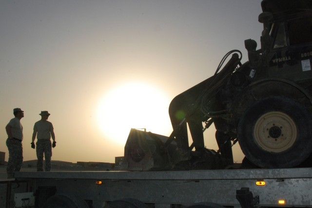 As the Sun sets at Camp Arifjan, Kuwait, Staff Sgt. Steven Trahan (left) and Sgt. 1st Class Brian May, 769th Engineer Battalion, Louisiana National Guard, supervise the offload of a FLU 419 Small Emplacement Excavator, June 20, 2008. The SEE is being prepared for shipment home as the 769th ends its service with the 4th Infantry Division in Iraq.