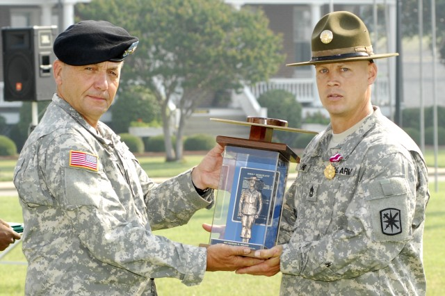 Lt. Gen. David Valcourt presents the trophy to Sgt. 1st Class Michael Noland, the 2008 Reserve Component Drill Sergeant of the Year. Noland represented the 95th Reserve Division in the competition. Each of the winners were awarded the Meritorious Service Medal and will be assigned at HQ TRADOC for the next year.