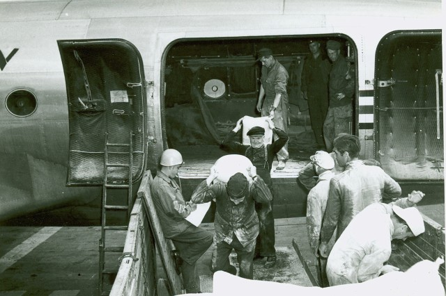 """""""German crews offload supplies from a C-54 at Templehof, 1 Mar 1949"""" [Helga Th. Mellmann Collection]."""