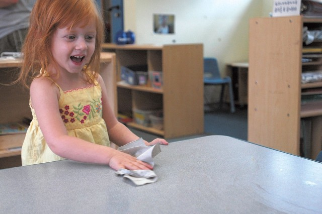 Paige Broussard cleans a table in her classroom at the Patrick Henry Village Child Development Center in Heidelberg, Germany, before her classmates join her for snack. Sharing in the communal responsibilities of the classroom teaches the children about relationships and their responsibilities as a member of the class.