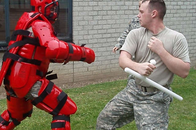 Sgt. Gerold Westley, right, takes a swing at Sgt. Sean Kolar, who is wearing a Redman suit during training exercises at U.S. Army Garrison Schinnen, Netherlands. Made of thick foam, the suit allows the wearer to withstand blunt force without harm. The newly acquired suit is now part of self-defense training for Schinnen military policemen.