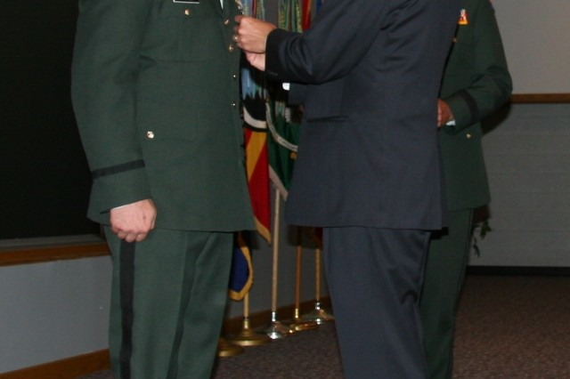 "Utah Governor Jon M. Huntsman Jr., pins the Bronze Star with ""V"" device on Capt. Chad A. Pledger, 19th Special Forces Group, Utah National Guard, during a ceremony June 19 in Draper, Utah."
