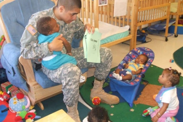 Spc. Rogelio Viera, Fort Story garrison commander's driver, reads the book Happy Birthday U.S. Army to infants in room three at the Fort Story Child Development Center June 11.