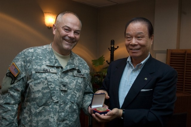 USAG-Yongsan Commander Col. Dave Hall (left) presents a medallion commander's coin to People-to-People New Seoul Chapter President Hwang Moo-young June 23 at an appreciation luncheon at Commiskey's Restaurant.