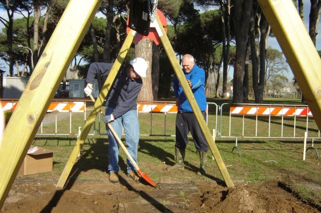 James Speck, left, digs an outline for a safety zone with his father, Barry Speck, at the Camp Darby playground outside of the Casa Toscana Army Lodge.