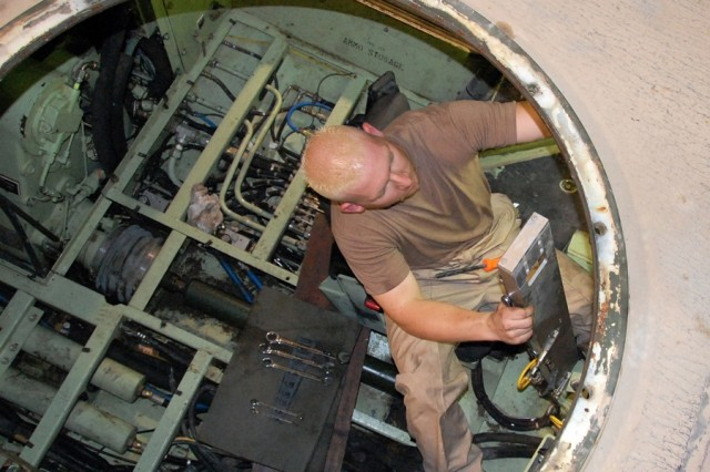 Heavy mobile equipment mechanic Carl Bess troubleshoots the driver's seat hydraulic assist mechanism for an M1117 Guardian, Armored Security Vehicle (ASV), June 18, 2008, at the 401st Army Field Support Brigade's ASV Repair Facility in Camp Arifjan, Kuwait. Bess is a Department of the Army Civilian employee, deployed to Southwest Asia from Red River Army Depot, Texarkana, Texas. The ASV Repair Facility receives battle-damaged or battle-weary M1117s from U.S. Army units in Iraq or Afghanistan, and returns them to operational status.